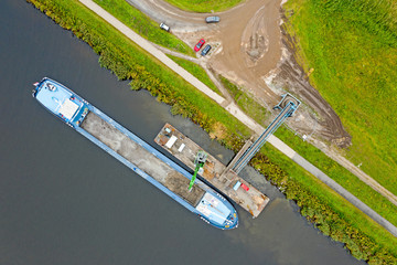 Aerial top shot from freighter unloading sand in the countryside from the Netherlands