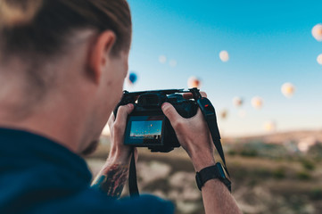 Young man photographer making pictures of air balloons at sunrise time in Cappadocia