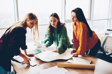 Three female designers dressed in casual wear collaborating on sketches in office.Pensive young professional architects working on building project standing at desktop with blueprints in studio Fototapete