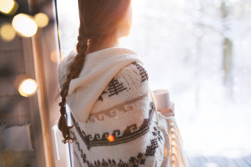 Foto op Plexiglas Cappuccino Thoughtful young brunette woman wearing nordic print poncho looking through the window, blurry winter woods snow landscape outside