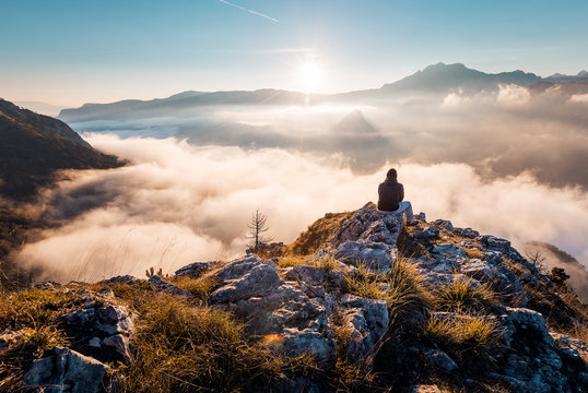 Man sitting an top of mountain at sunrise and enjoying the view