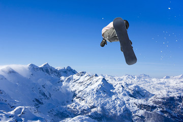 Skier Snowboarder jumping through air with sky in background