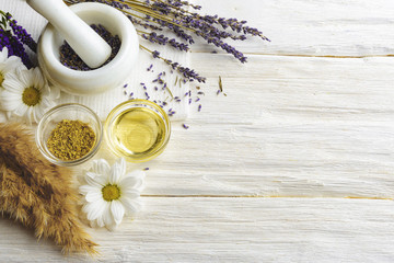 Composition with dried lavender flowers in white marble pestle and mortar and natural chamomile oil cosmetic in glass jar on white background, top view with free copy space