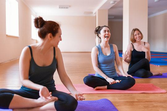 A group of young women have fun chatting with each other after a workout. The concept of sport, yoga and socialization. Close up