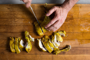 Hands cutting Chinese style chicken legs on wooden cutting board