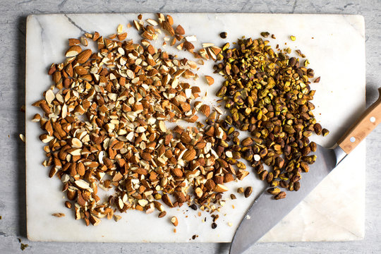 Overhead view of almonds and pistachios on cutting board