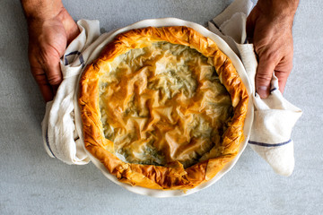Overhead view of hands holding spinach and feta borek pastry