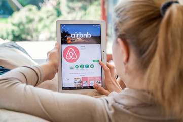 WROCLAW, POLAND- APRIL 10th, 2017:  Woman is installing Airbnb application on Lenovo tablet. Airbnb is an online marketplace and hospitality service, enabling people to rent lodging