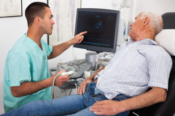Doctor pointing to monitor during examination a man with ultrasound