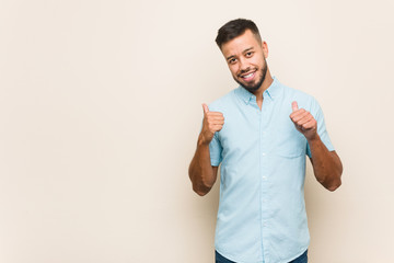 Young south-asian man raising both thumbs up, smiling and confident.