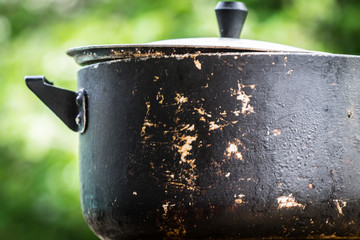 A dirty old metal pot. Close-up photo.