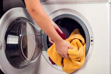 Loading clothes in washing machine. Housework and laundry concept