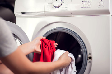 Loading white and color clothes in washing machine. Washing clothes in different colors at the same time