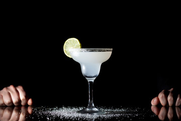 bartender serves classic margarita with lime on a black background