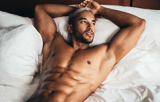 Sexy man in bed in hotel room
