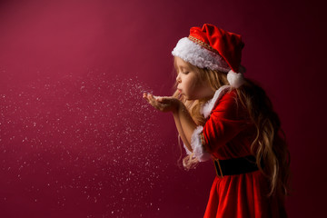little blonde girl in a Santa suit blows snow off her hands. red background isolate. space for text