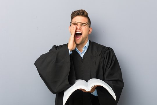 Young jurist holding a book shouting excited to front.