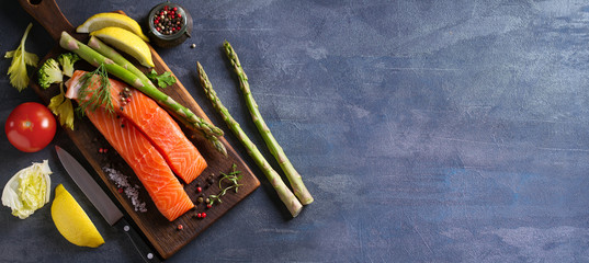 Fresh raw salmon fish fillet, asparagus, lemon, herbs and spices. View from above, top. Copy space