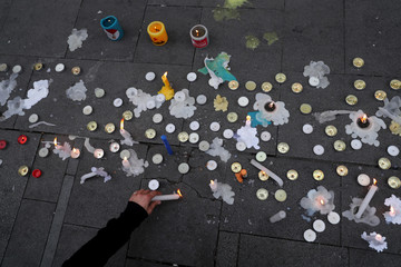 A person lights a candle before taking part in a demonstration, in Santiago