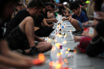 People light candles before taking part in a demonstration, in Santiago