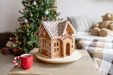 Gingerbread house on table with red coffee cup, concept holiday of Christmas and Happy new year....