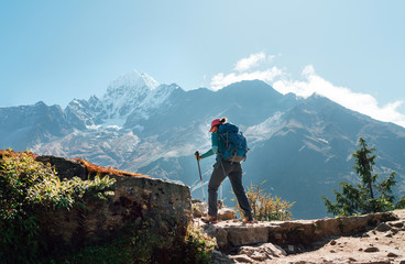 Young hiker backpacker woman using trekking poles enjoying Everest Base Camp trekking route with Thamserku 6608m mountain on background during high altitude Acclimatization walk in Sagarmatha NP,Nepal