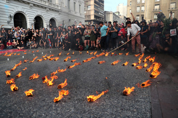 People light candles during a demonstration in Santiago