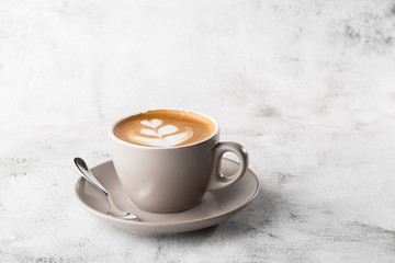 Foto op Plexiglas Cafe White cup of hot latte coffee with beautiful milk foam latte art texture isolated on bright marble background. Overhead view, copy space. Advertising for cafe menu. Coffee shop menu. Horizontal photo.
