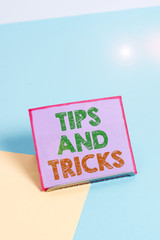 Word writing text Tips And Tricks. Business photo showcasing helpful advices that makes certain action easier to do Paper placed tilted above buffer wire on soft pastel multi colours backdrop