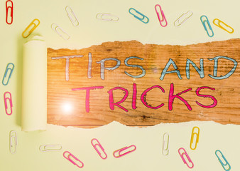 Writing note showing Tips And Tricks. Business concept for helpful advices that makes certain action easier to do Paper clip and torn cardboard on wood classic table backdrop