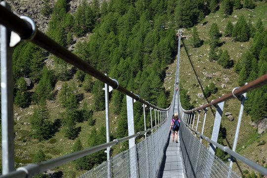 girl crossing the Charles Kuonen Suspension Bridge in Randa, Switzerland