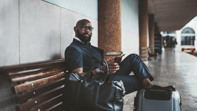 A mature African bald bearded man entrepreneur waiting for a train to start his business trip and sitting on the wooden bench at the platform of a railway station with a smartphone and bags near him