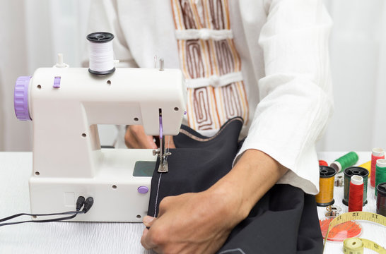 Sewing with black fabric by using small sewing machine and accessories for sewing on table