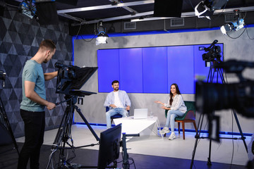 Obraz Presenters and video camera operator working in studio. News broadcasting - fototapety do salonu
