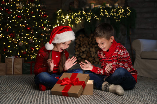 Happy children with magic Christmas gift on floor at home