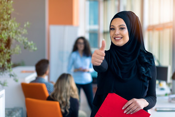 Cheerful woman in the office, holding folder with documents and giving a bright smile. Muslim women employment.
