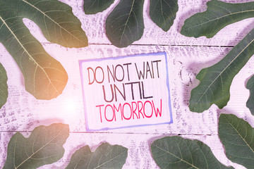 Handwriting text Do Not Wait Until Tomorrow. Conceptual photo needed to do it right away Urgent Better do now Leaves surrounding notepaper above a classic wooden table as the background