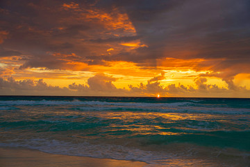 Dramatic sky during sunrise hour. Picture taken on a cloudy and windy day in November  in Cancun, Mexico over Caribbean sea.