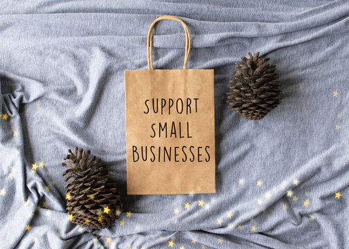 """Support small businesses"" text on a plain brown paper bag flat lay with pine cones and stars - Christmas shopping message concept"