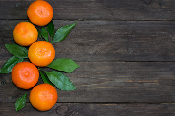 Fresh orange mandarins with green leaves on a dark wooden table. The concept of a healthy diet and vegetarianism. Top view.