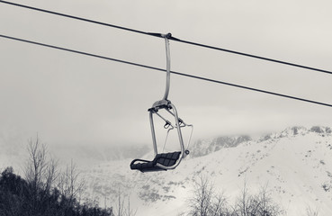 Fototapete - Chair lift and snowy mountains in haze