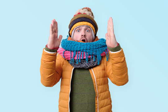 Smiling millennial Caucasian man in winter hat and scarf show big size with both hands