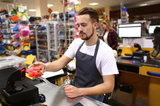 Male cashier checking out goods in supermarket