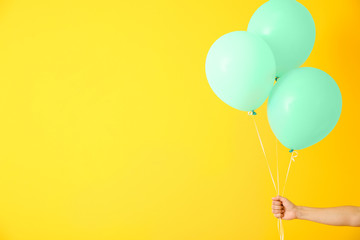 Female hand with air balloons on color background
