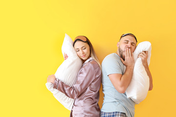 Sleepy young couple with pillows on color background