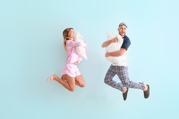Jumping young couple with pillows on color background
