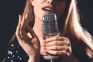 Beautiful young female singer with microphone on stage, closeup