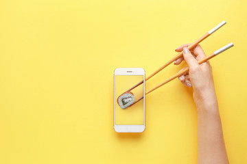 Female hand holding chopsticks and mobile phone with tasty sushi roll on screen against color background