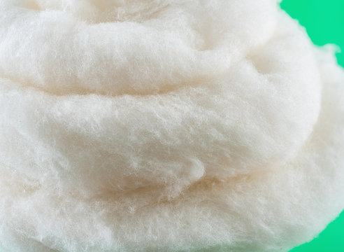 Closeup of long-staple cotton material detail on green background