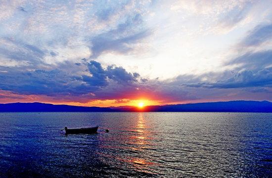 Boat in scarlet sunset on Ohrid Lake in September